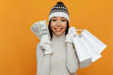 Money. Shopping. Woman portrait. Accessories. Asian girl in a white polo neck, cap and gloves is holding money and shopping bags and smiling, on an orange background