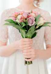 Female hands holding wedding flowers. Wedding ring and brides's dress.