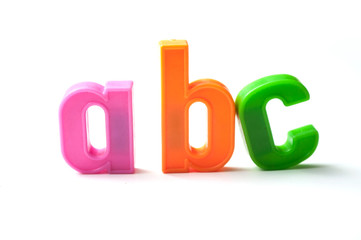 closeup of colorful plastic letters on white background - abc