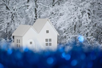 Small white cardboard houses, winter snowy trees background, blue bokeh effect. Handmade home winter decoration. Do it yourself. Shallow depth of focus.
