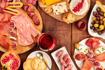Charcuterie. A photo of various sausages and hams, deli meats, and a cheese platter, shot from above on a dark rustic background with a glass of red wine, olives and a place for text