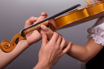 Hands of a teacher of playing the violin correct little pupil on gray background