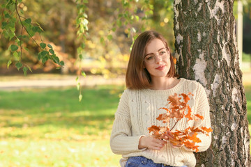 Beautiful young woman near tree in autumn park