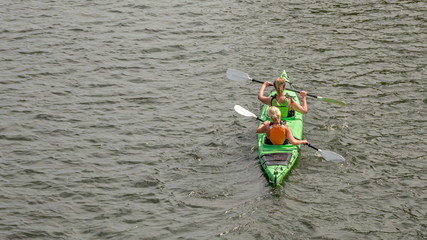 Two blondy woman sitting in kayak, paddling in the sea water, back view, horizontal, copy space