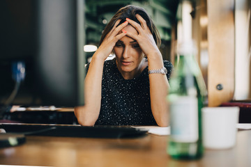 Frustrated female computer programmer with head in hands at office desk