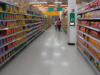 Blurred people shopping in selection of Snack on shelf in supermarket or department store, products on shelves
