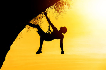 Obraz Silhouette of man climbing at sunset. The rock climber during ro - fototapety do salonu