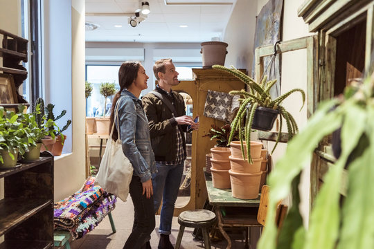 Smiling couple looking at wall decor while shopping in boutique