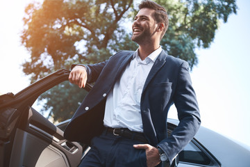A young handsome man in a suit comes out of the car and laughs