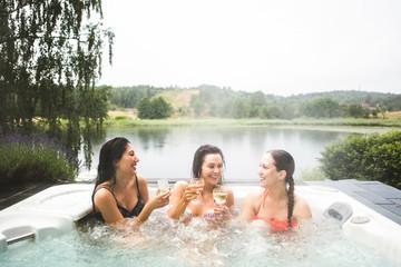 Cheerful female friends enjoying wine in hot tub against lake during weekend getaway