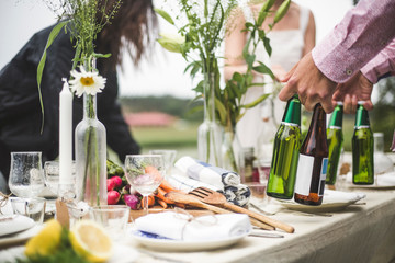 Cropped image of man holding beer bottles at dining table during dinner party in backyard