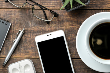 Smartphone white and a cup with coffee glasses and a notepad on a brown wooden table. view from above
