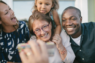 Cropped image of man showing mobile phone to happy family on porch