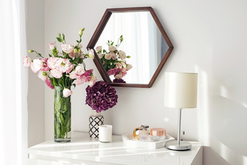 Light room with mirrow, flowers, night lamp and other objects