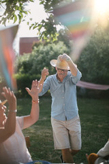 Senior woman clapping while man wearing straw hat and walking in backyard during sunny day