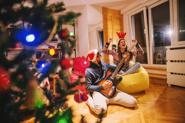 Man playing electric guitar to his girlfriend. On heads reindeer headband and santa's hat. In foreground Christmas tree and presents. Christmas holidays concept.