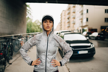 Portrait of confident female athlete in wet hooded jacket standing on sidewalk in city
