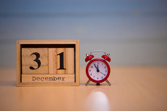 December 31st on wooden calendar and red alarm clock with blue background