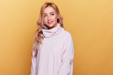 Young cheerful woman with long blonde wavy hair and in light pink sweater standing on yellow...