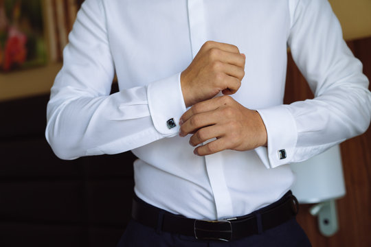 Closeup businessman puts on cufflinks, wears expensive leather belt. Man in a business suit, white shirt. Preparing the groom on the wedding day
