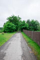 asphalt road near wooden fence