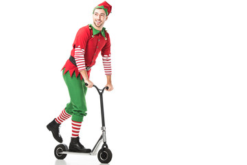 Fototapeta cheerful man in christmas elf costume riding push-cycle and looking away isolated on white