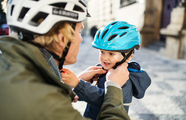 A young father putting on a helmet on his toddler son's head outdoors in city. Wall mural