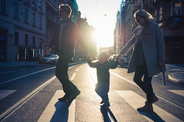 A small toddler boy with parents crossing a road outdoors in city at sunset.