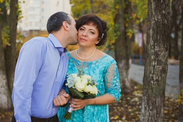 Mature plus size bride with groom at park, life of middle aged women. Concept of marriage with younger man