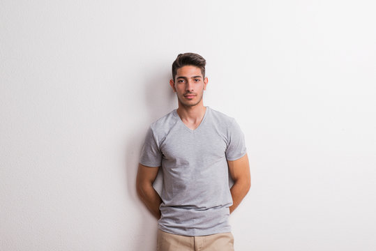 A cheerful young hispanic man standing in a studio.
