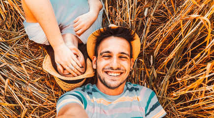 Beatiful couple smiling at the camera taking a selfie lying on a wheat field
