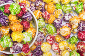 background of multicolored popcorn and paper cup, close-up, top view