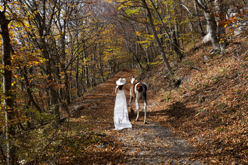 Woman in a white dress and hat and horse in the autumn forest