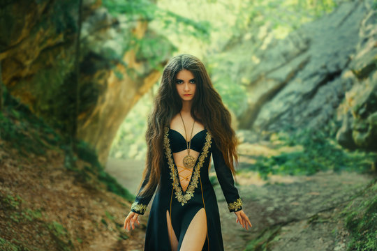 gorgeous mysterious priestess of a dark clan with lush long hair in an amazing black dress with an open chest and legs, necklace on her neck, looking at the camera with a stern look in green forest