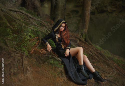 Witch With Red Hair In A Long Black Dress With Open Legs Hooded