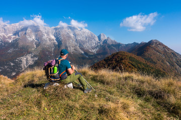 Man hiker sit and watch the landscape of  mountain in autumn from the mountain top.