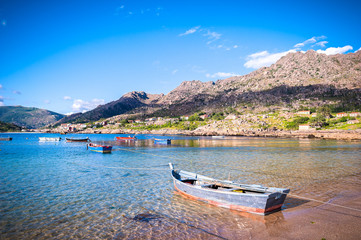 Beauty Atlantic coast with fishing boats, beach, ocean, village, mountains and sky with clouds. Galicia, Spain.