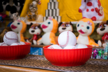 Close-up of baseball balls for the game of throw at jars in a fair. In the background the jars and the prize puppets.