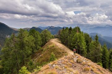 Hiker walks on the mountain ridge under a stormy sky.