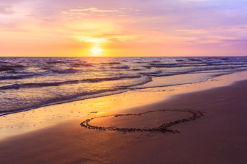 Heart shape drawn on a sandy beach at sunset