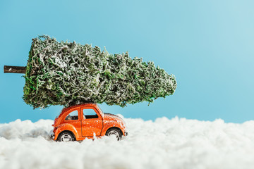 side view of toy vehicle with miniature christmas tree on rooftop riding by snow made of cotton on blue background