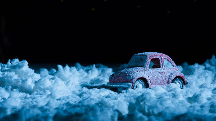 close-up shot of miniature car standing in snow in night