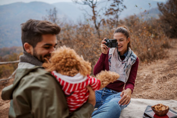 Woman taking photo of her boyfriend and dog while sitting on blanket at picnic.