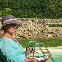 A lady artist sits in sunshine beside a swimming pool working on the painting she started earlier in the day.
