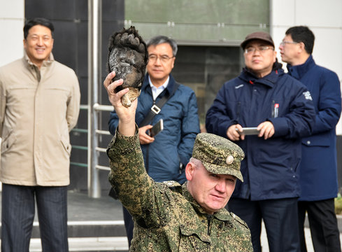 Mikhail Mos, head a of a custom's canine department, holds a bear paw confiscated from smugglers and currently used for training sniffer dogs, in front of custom officers from China during a workshop in the far eastern city of Vladivostok