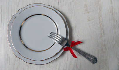 two white plates with a gilded cut edge and a fork with a red bow on a wooden background. festive table setting