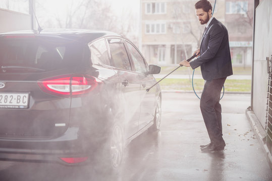 Businessman washing his car in car wash. Serious facial expression.