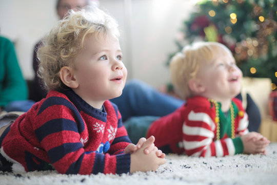 Lovely twins sitting on the carpet, wearing christmas clothes