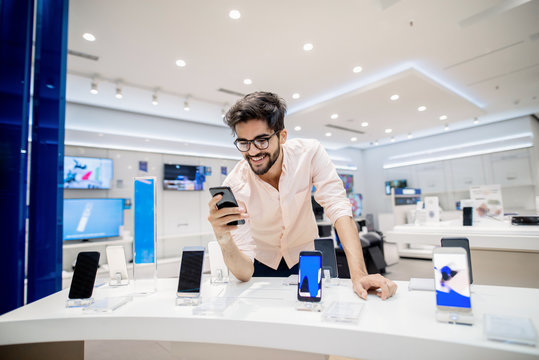 Man trying out new smart phone. Tech store interior.