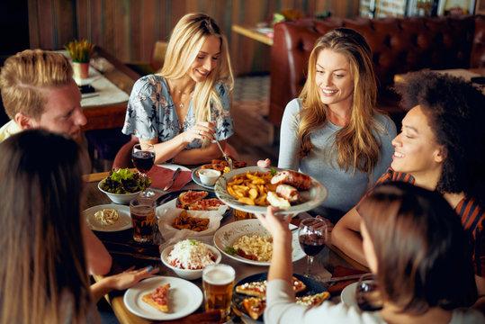 Friends having dinner at restaurant. Multi ethnic group.